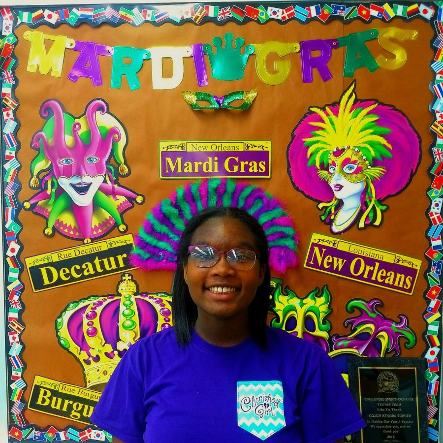 Standing in front of a Mardi Gras display, sophomore Zyaiah Harvey thoroughly enjoyed participating in Mardi Gras practices.